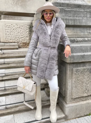 Model stood outside on stone steps wearing Glamify Claudia Faux Fur coat in grey and carrying a cream handbag