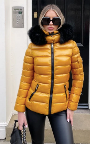 Model wearing Glamify Elissa Padded coat in mustard with black faux fur trim and carrying a black handbag