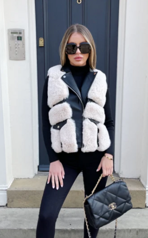 Model stood outside a house with a black door wearing Glamify Eliza gilet with black and cream faux fur.