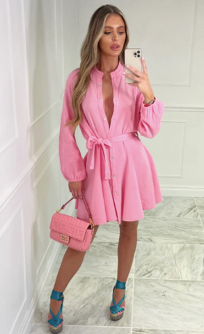 Model wearing Glamify Emmie Pink Tie Waist Dress with blue heels and a pink Fendi handbag