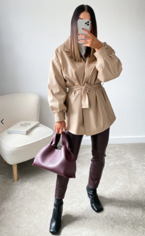 Model wearing Glamify Eva trenchcoat in PU, with leather trousers and boots