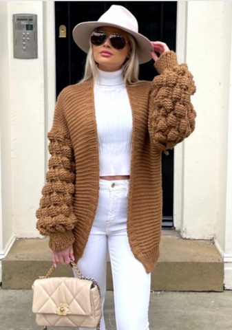 Model wearing Goldie camel bobble sleeve knitted cardigan over a white high neck top, white trousers and a white trilby hat