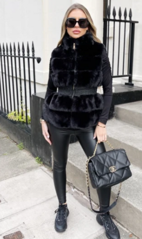 Model stood in front of black railings wearing Glamify Imogen gilet with black faux fur.
