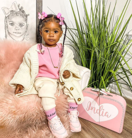 Model shot of a toddler in a white tracksuit and pink top sat on a fur covered seat