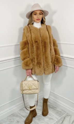 Model in a studio wearing Glamify Iris Faux Fur coat in camel and carrying a cream handbag