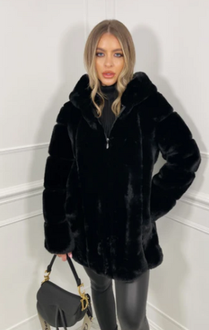 Model in a studio wearing Glamify Italia Faux Fur coat in black and carrying a black handbag