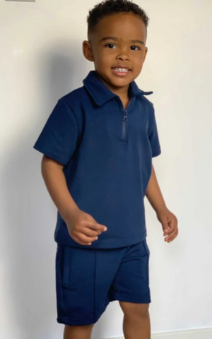 A young boy with smiling while dressed in Glamify Kids David two piece short set in navy blue