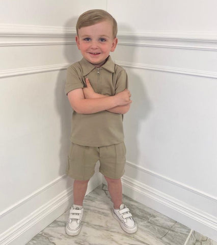 A young boy with crossed arms smiling while dressed in Glamify Kids David two piece short set in stone