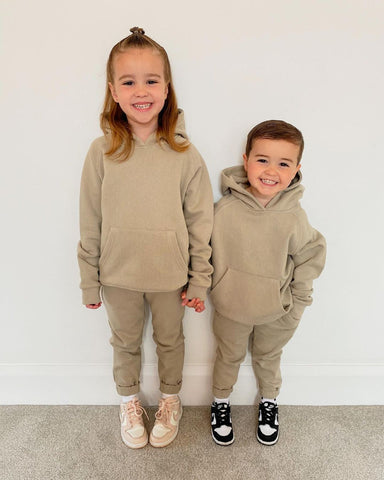 A young boy and girl holding hands and smiling while dressed in Glamify Kids Alex two piece set in stone