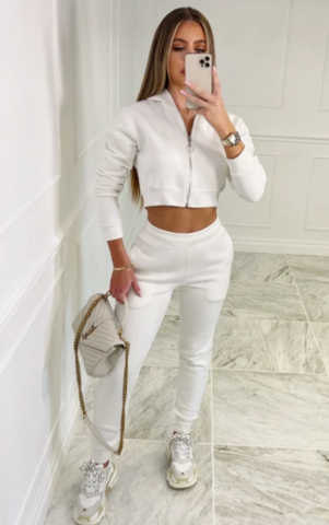 Model wearing Glamify Lara cream two piece loungewear and holding silver bag