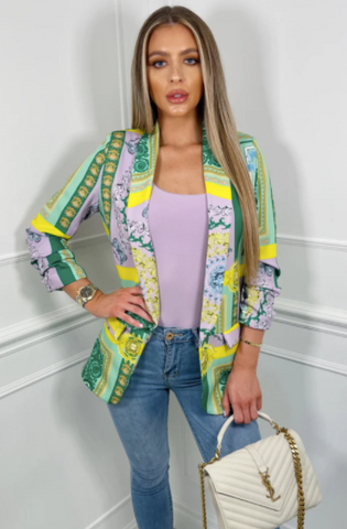 Model wearing Glamify Luciana green print ruched sleeve blazer, with jeans and holding a white Chanel bag.