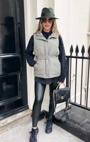 Model stood outside a house with a black door wearing Glamify Macy khaki belted gilet.
