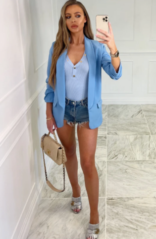 Model wearing Mia blue ruched long sleeve blazer with denim shorts, holding a cream Chanel bag