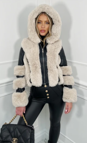 Model in a studio wearing Glamify Reeve Faux Fur coat in black and white and carrying a black handbag