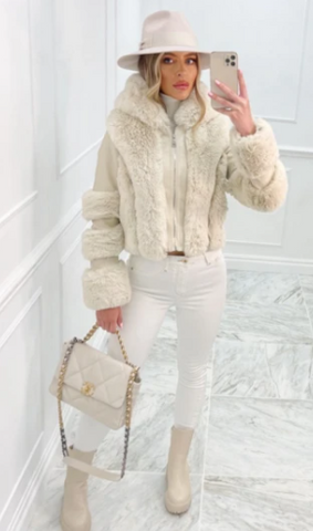 Model in a studio wearing Glamify Reeva cropped Faux Fur coat in cream and carrying a cream handbag