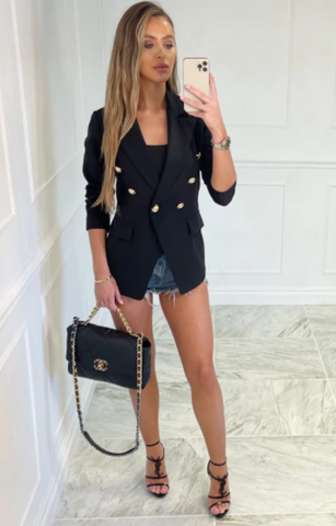 Model wearing Glamify Maddie black button up long-sleeve blazer with cut off denim shorts and holding a black Chanel bag.