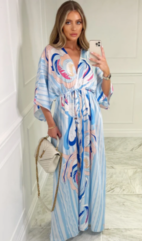 Model wearing Glamify Woowoo maxi dress in blue pattern and holding a Chanel bag