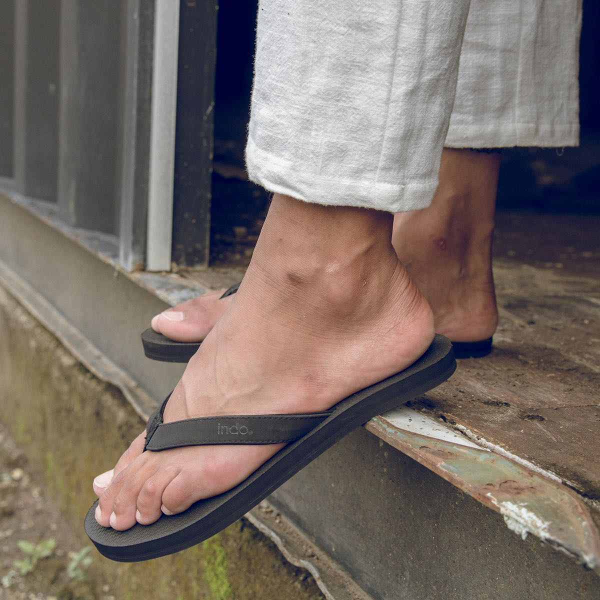 Man wearing black flip flops with white pants in Bali