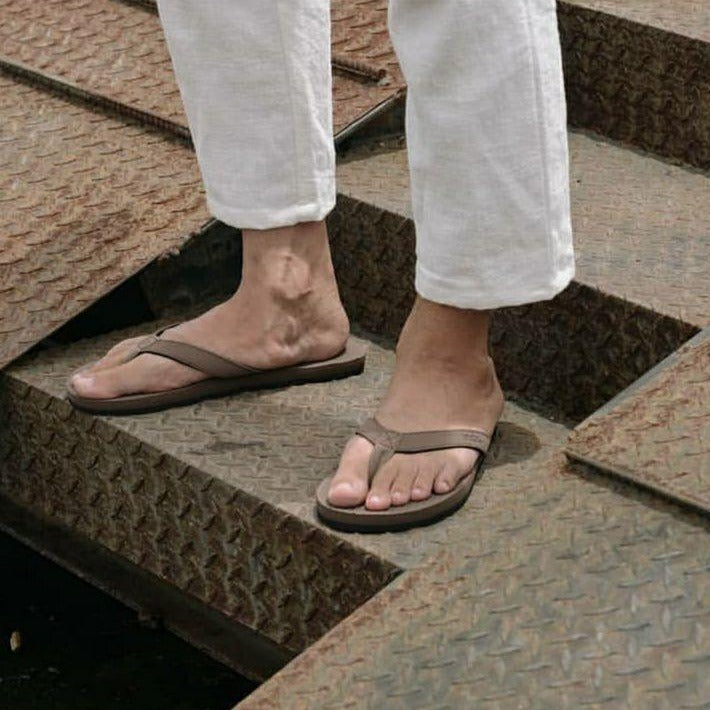 Man wearing soil flip flops and white pants standing on industrial metal stairs