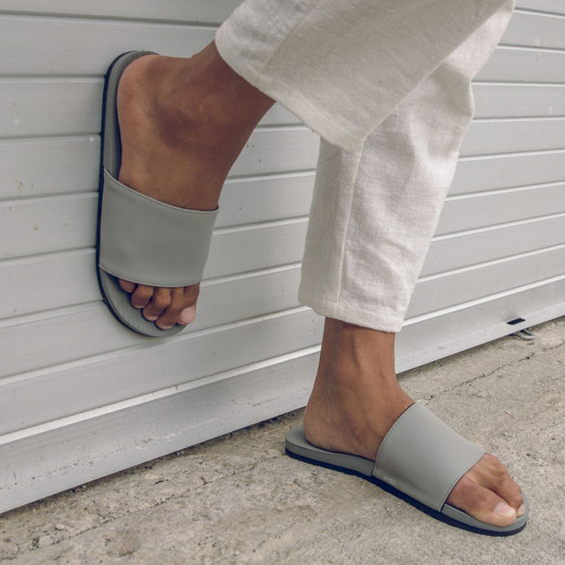 Man wearing granite slides with one foot on the ground and the other against the wall