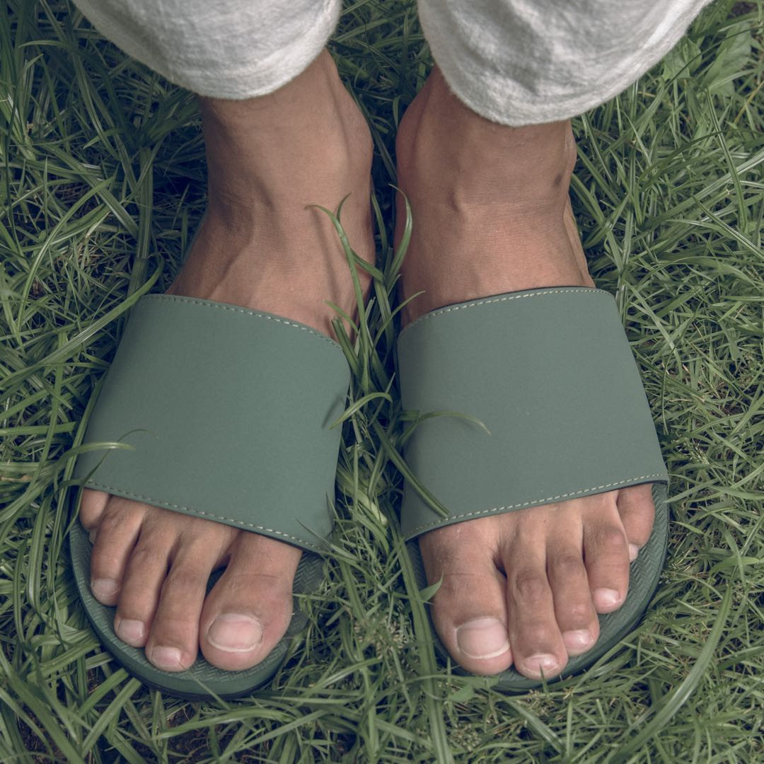 Man wearing leaf green slides standing on grass