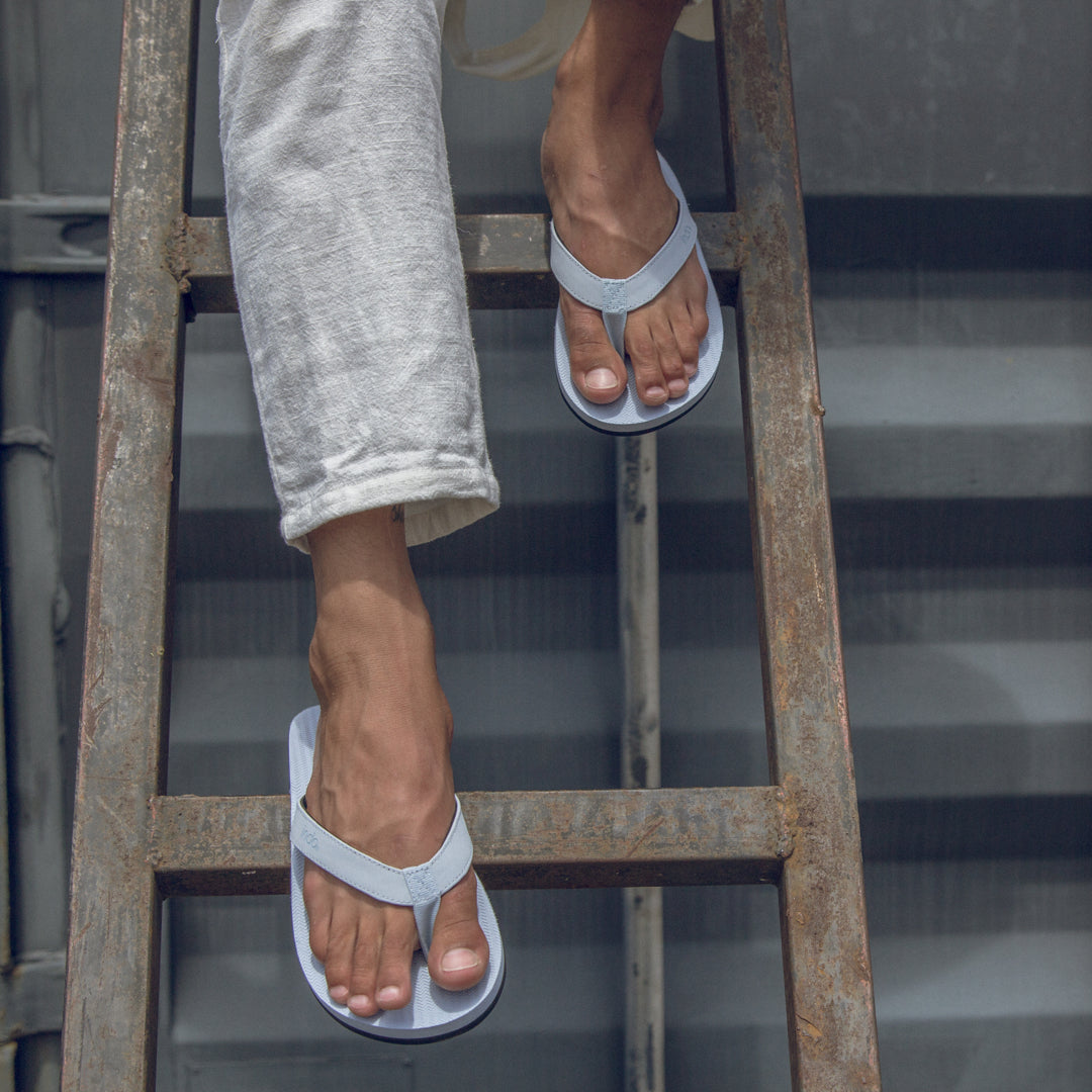 Man wearing light shore flip flops and white linen pants on a ladder