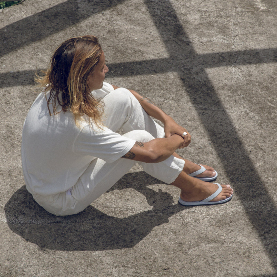 Man wearing light shore flip flops and matching white linen shirt and pants sitting on the floor on a sunny day
