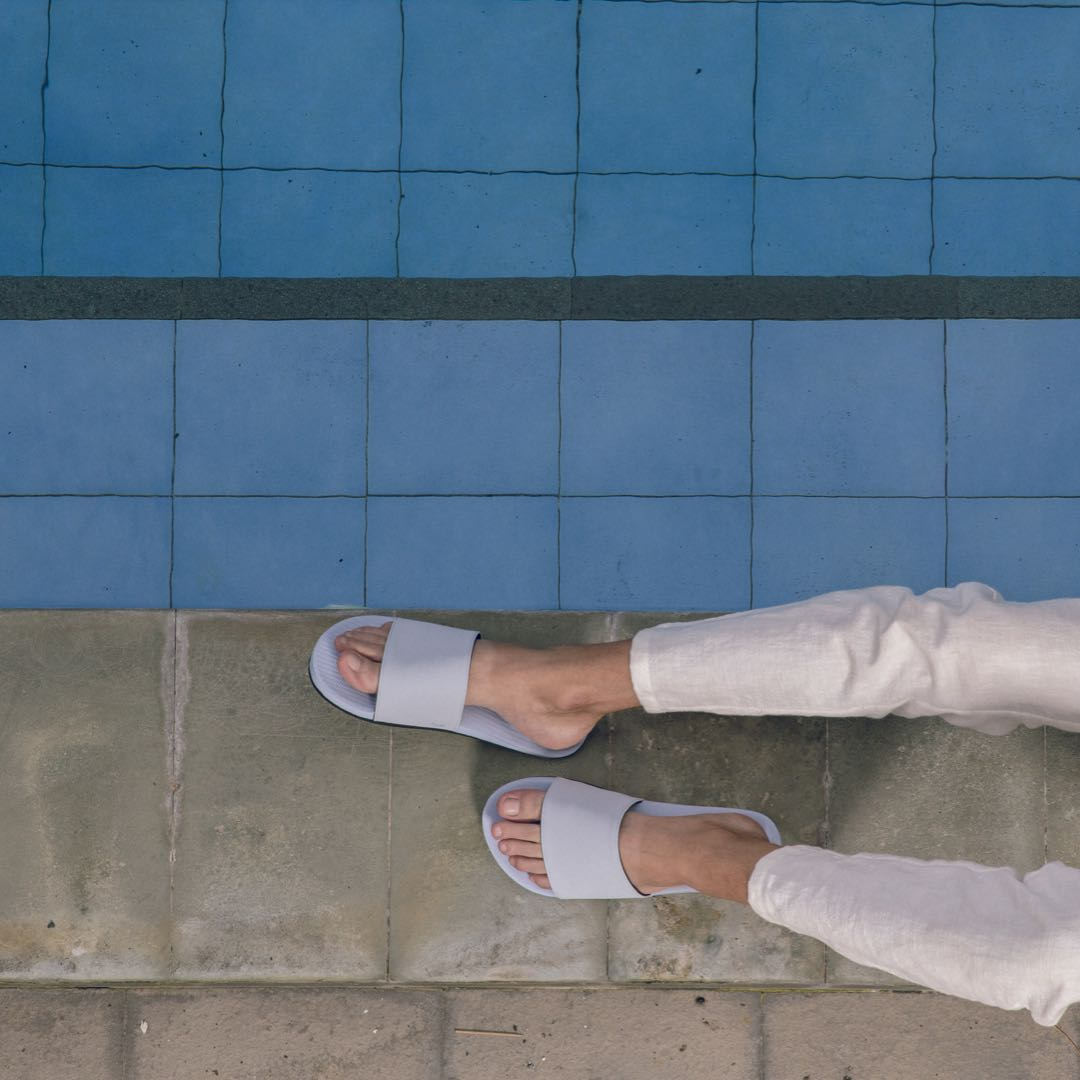 Man wearing light shore slides and white pants poolside