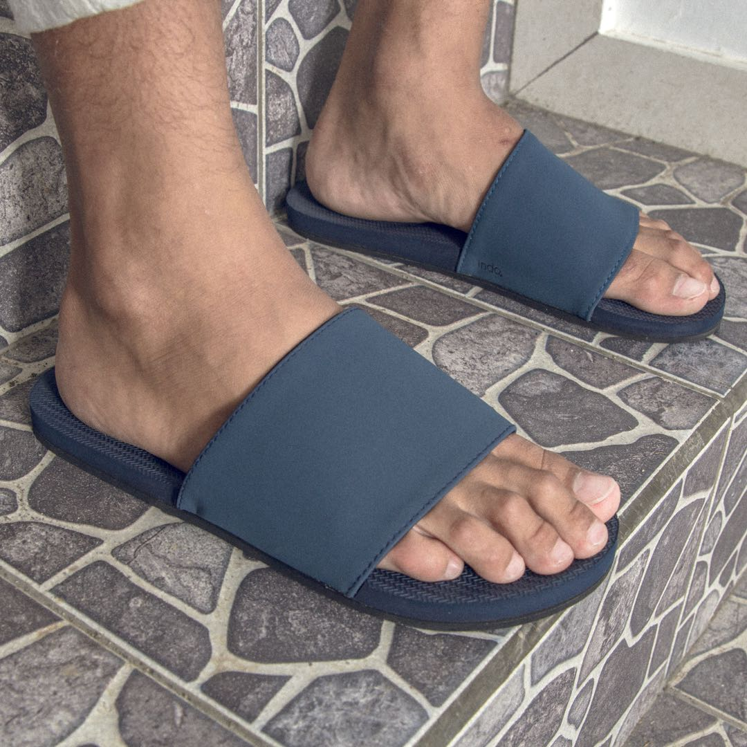 Man wearing shore slides on grey stone tiled stairs