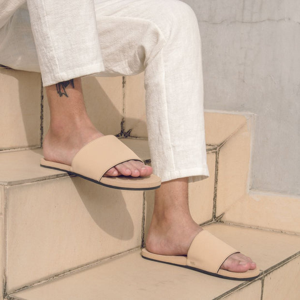 Man wearing light soil slides and white pants sitting on cream coloured stairs