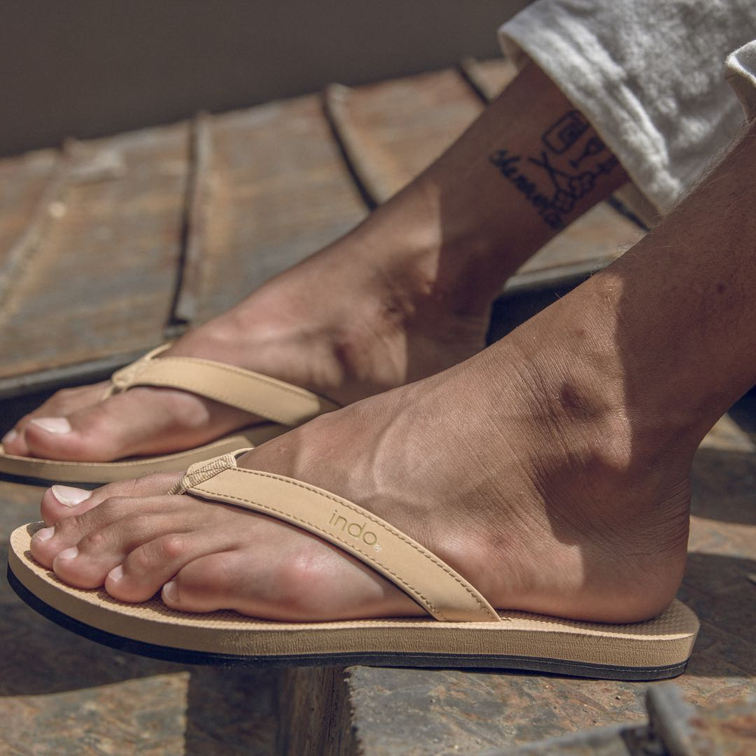 Man wearing light soil flip flops with an ankle tattoo