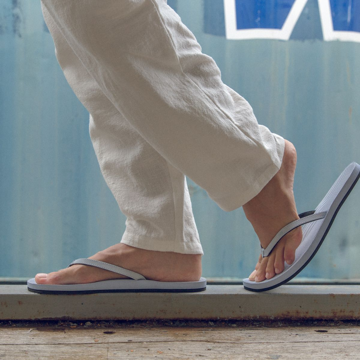Woman wearing light shore Indosole flip flops and white pants