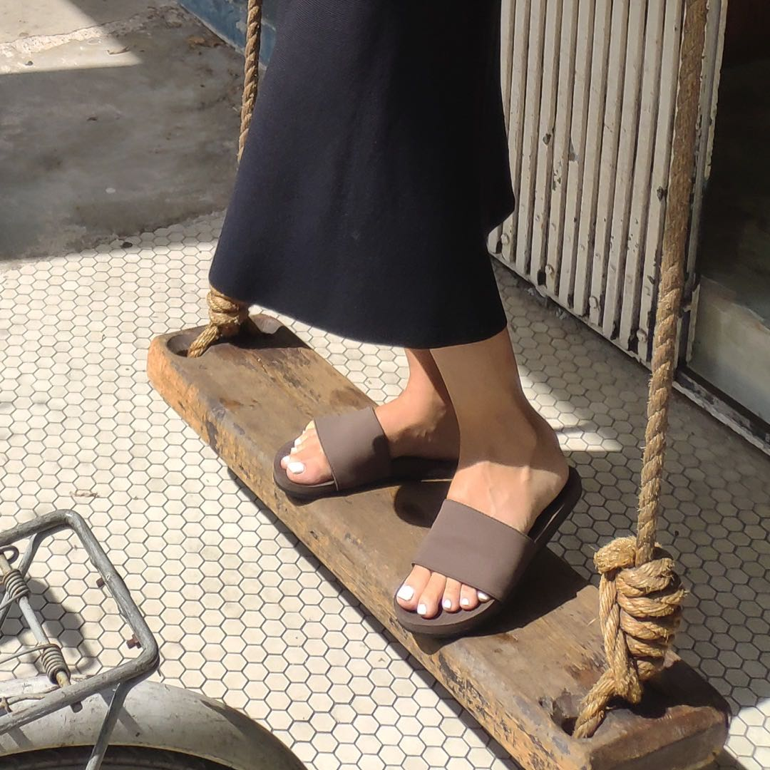 Woman wearing soil slides standing on a wooden swing