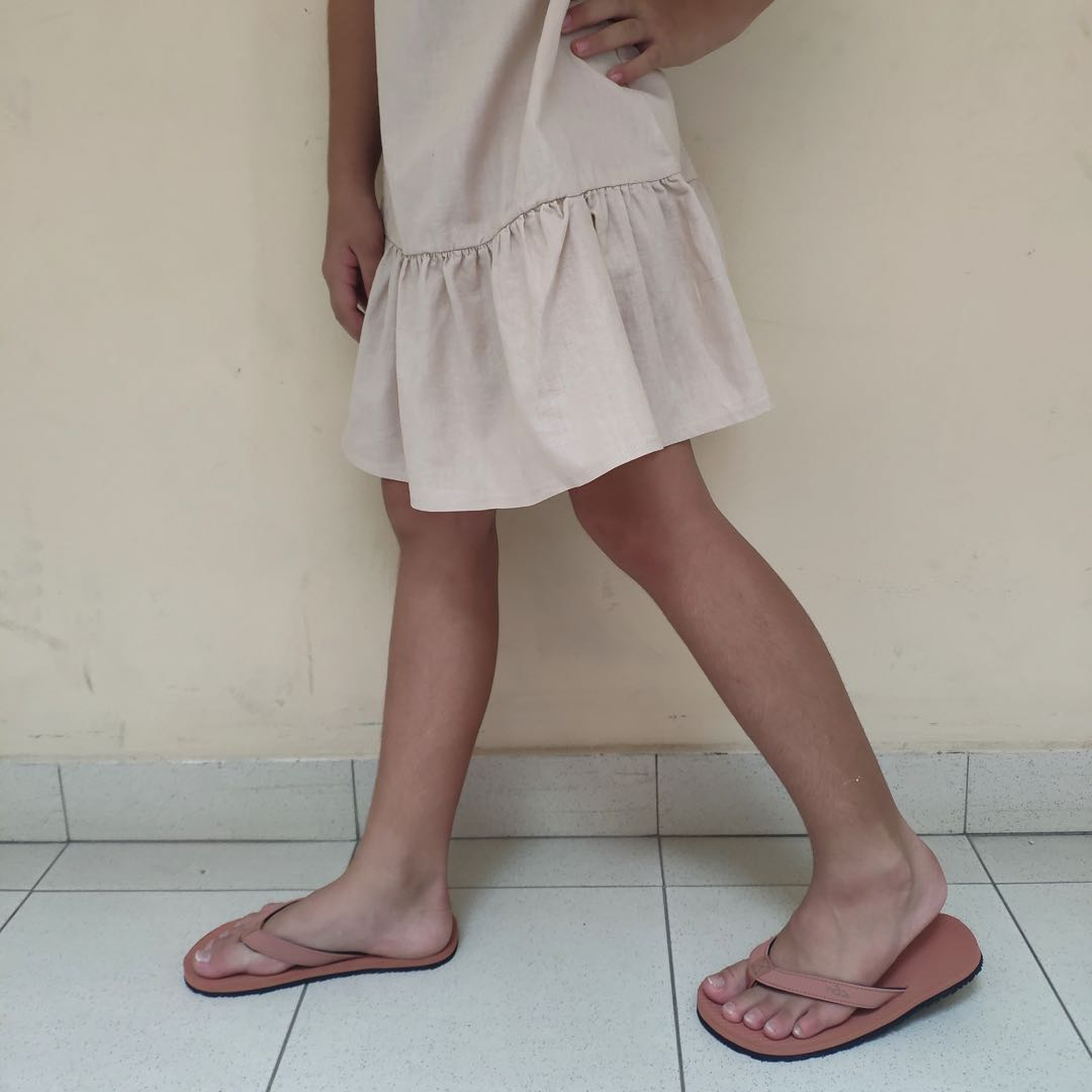 Girl wearing white dress and rust flip flops