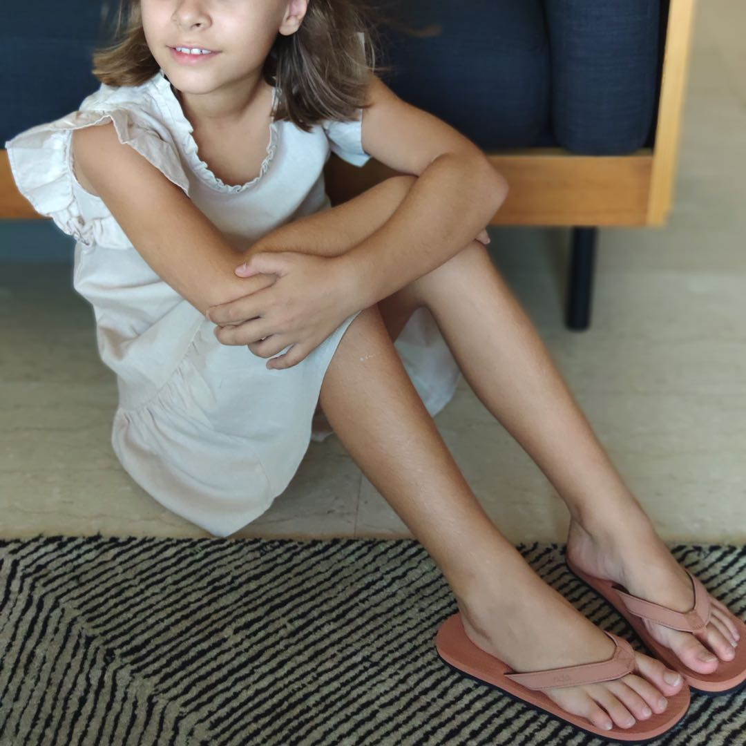 Girl sitting on the floor in a white dress wearing rust flip flops