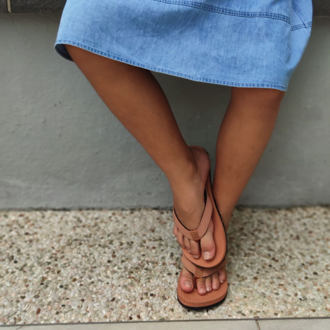 Girl wearing rust flip flops and a blue dress