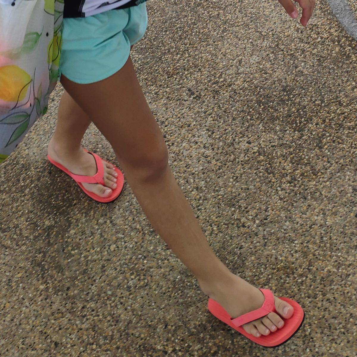 Girl wearing coral flip flops and blue shorts