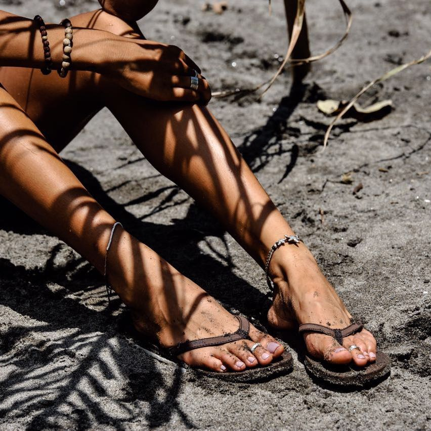 Woman wearing soil flip flops sitting on wet sand with leaf shadows over her legs