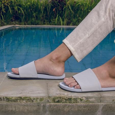 Man wearing light shore slides sitting poolside