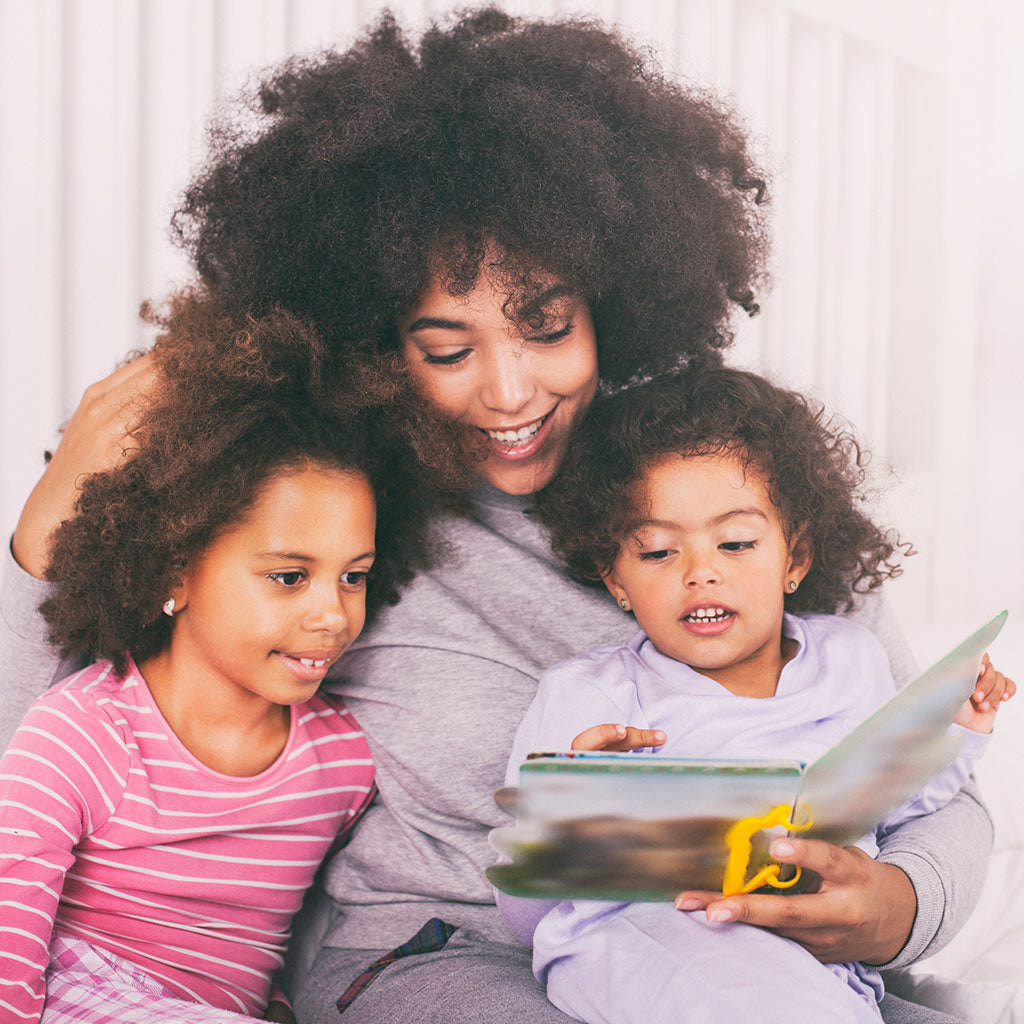 Mother reading a book to her two kids