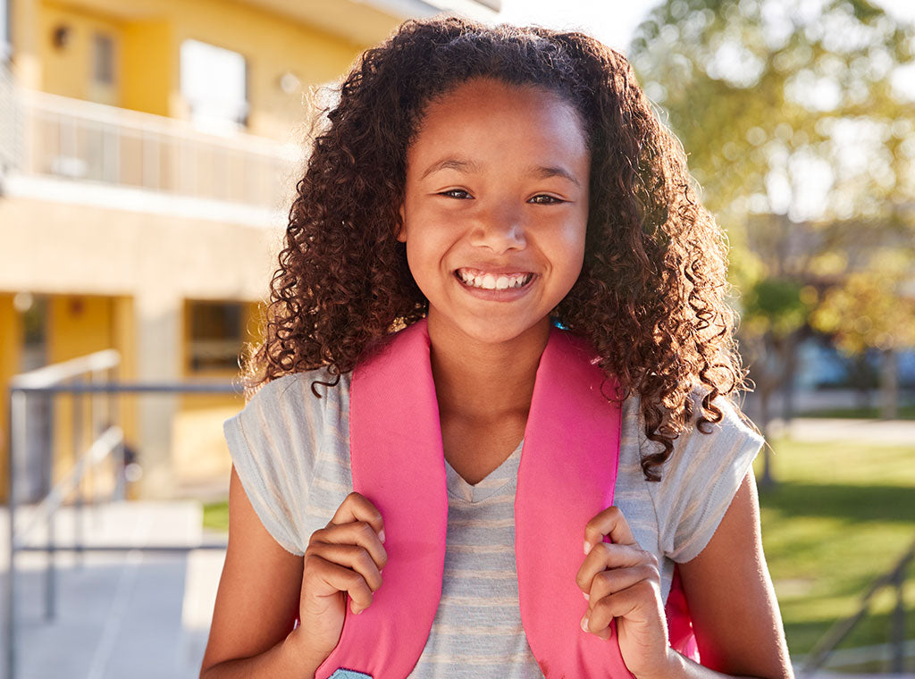 Girl with curly hair wearing a backpack