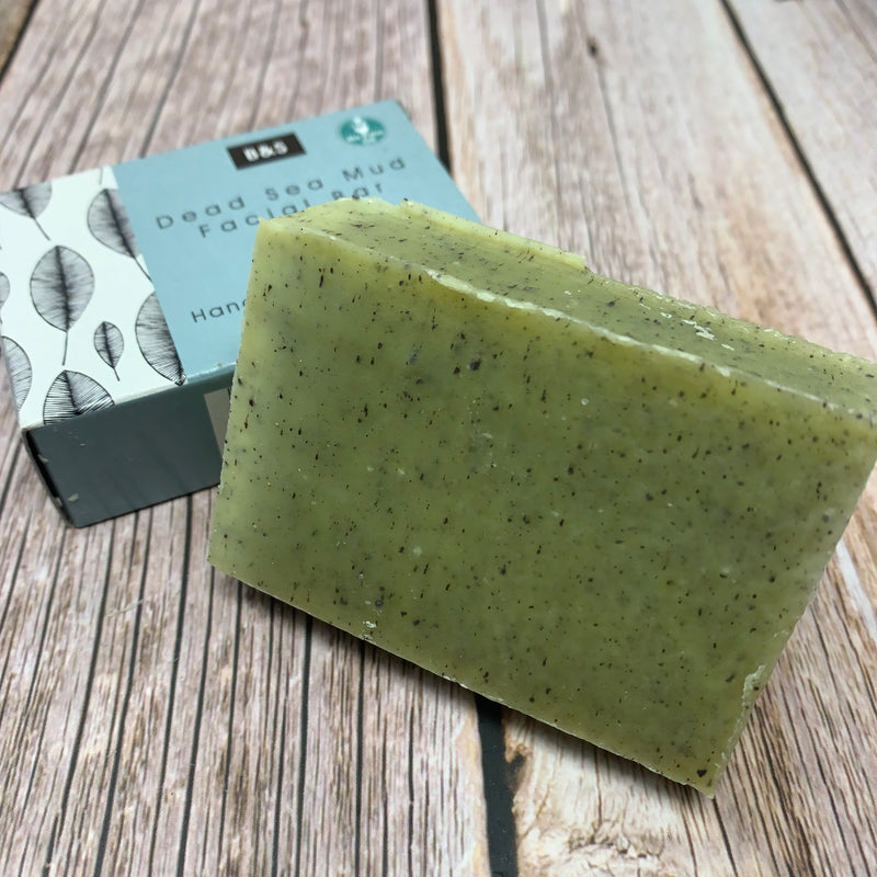 green dead sea mud facial soap bar with black small spots on surface
