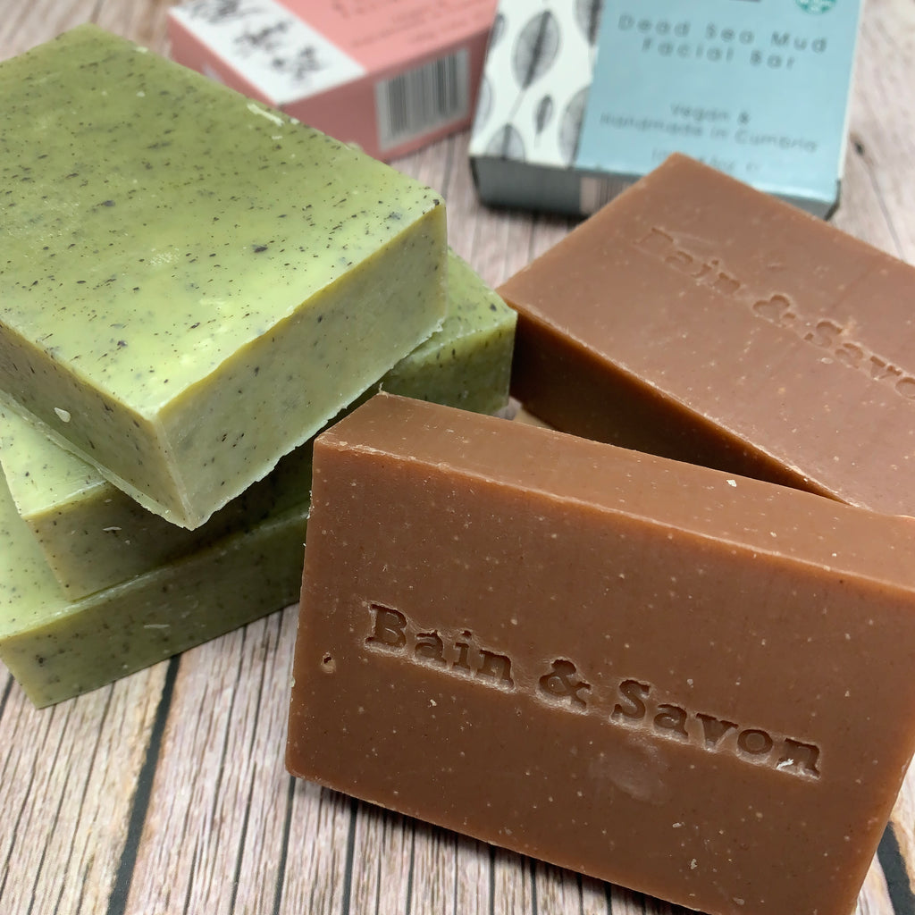 green and brown facial soap bars with bain & savon logo on one of the soaps