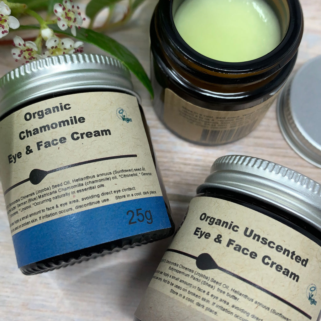 25g jars of organic eye and face cream, one organic chamomile moisturiser and one organic unscented one. One jar is opened to show inside of the tub