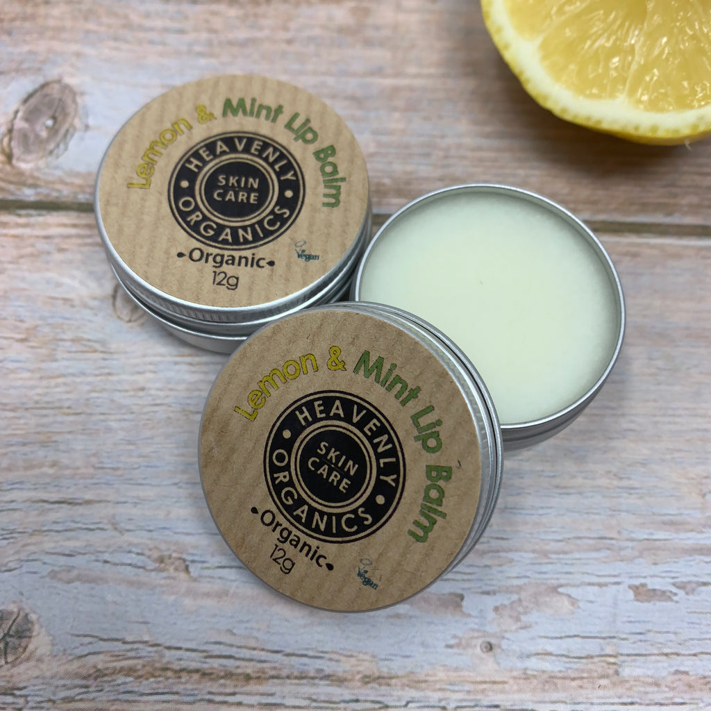 two moisturising lip balms with lemon and mint in reusable metal containers and brown paper label on a wooden table and a fresh lemon