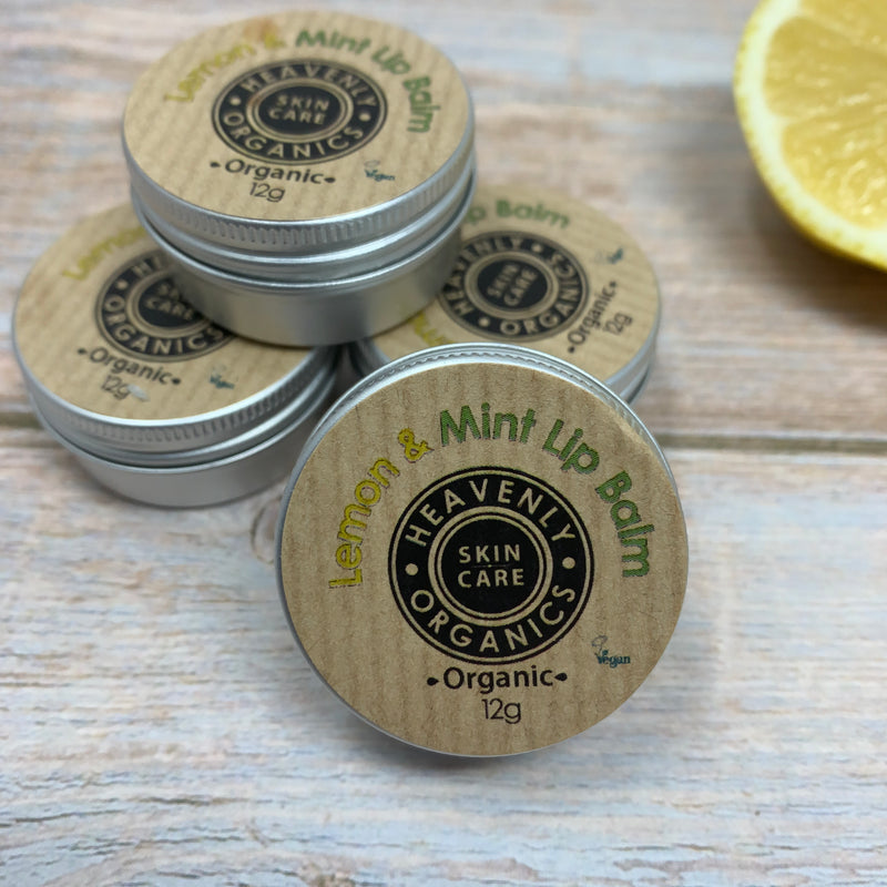 small containers of heavenly organics lip balms with metal box and recyclable brown label with yellow and green writing saying Lemon & Mint Lip Balm by Heavenly Organics