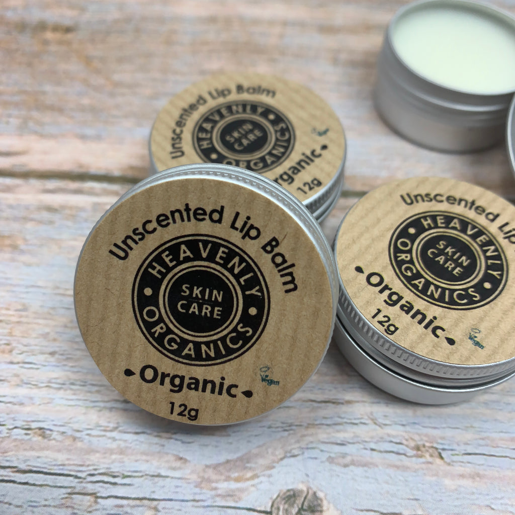 unscented lip balm by Heavenly organics in metal tin and paper label with black circular logo and open lip balm at the back