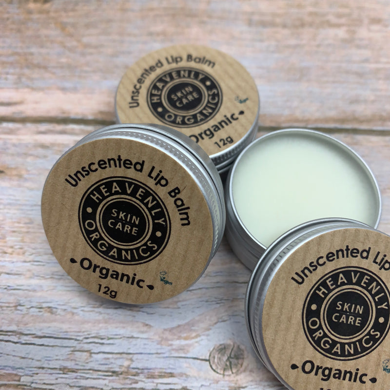 three unscented lip creams by heavenly organics, two sealed and one open showing white lip cream inside