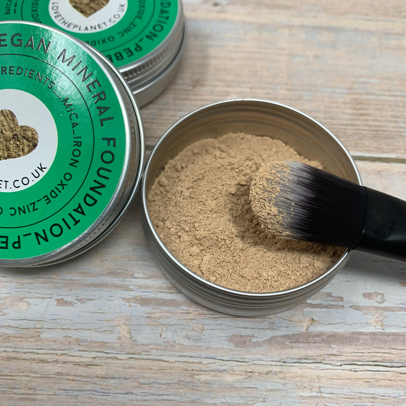 foundation brush dipped into foundation powder in round metal container and green lid with love the planet logo