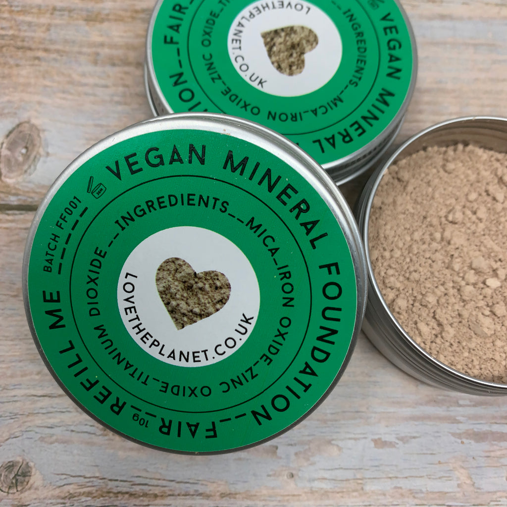 vegan foundation powder in reusable metal tins with green cap with little heart in the middle with the colour of the foundation powder